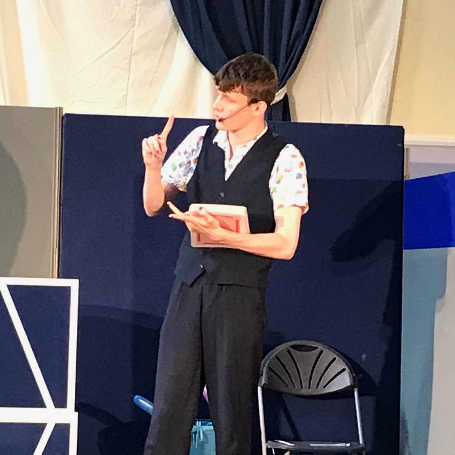Image of Harvo performing a magic trick live on stage