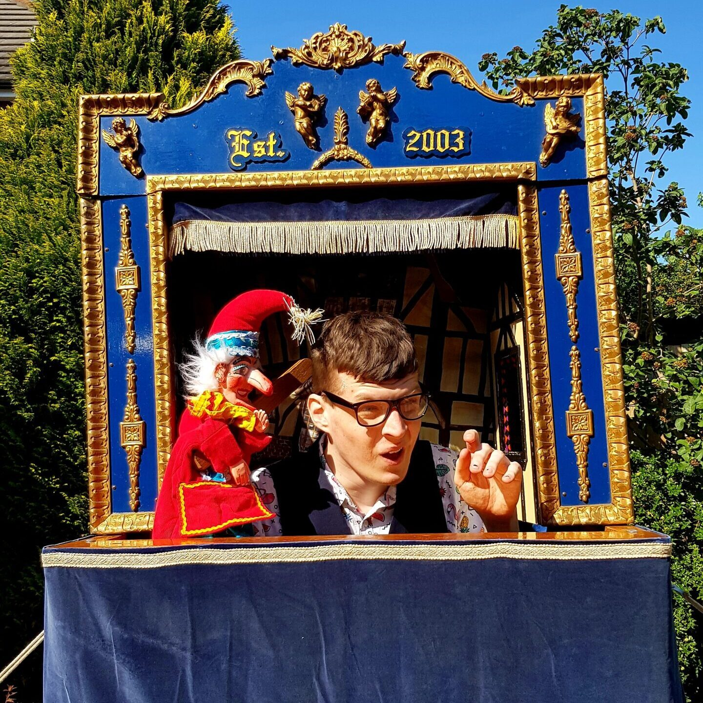 Mr Punch hitting Harvo inside the Punch and Judy Theatre