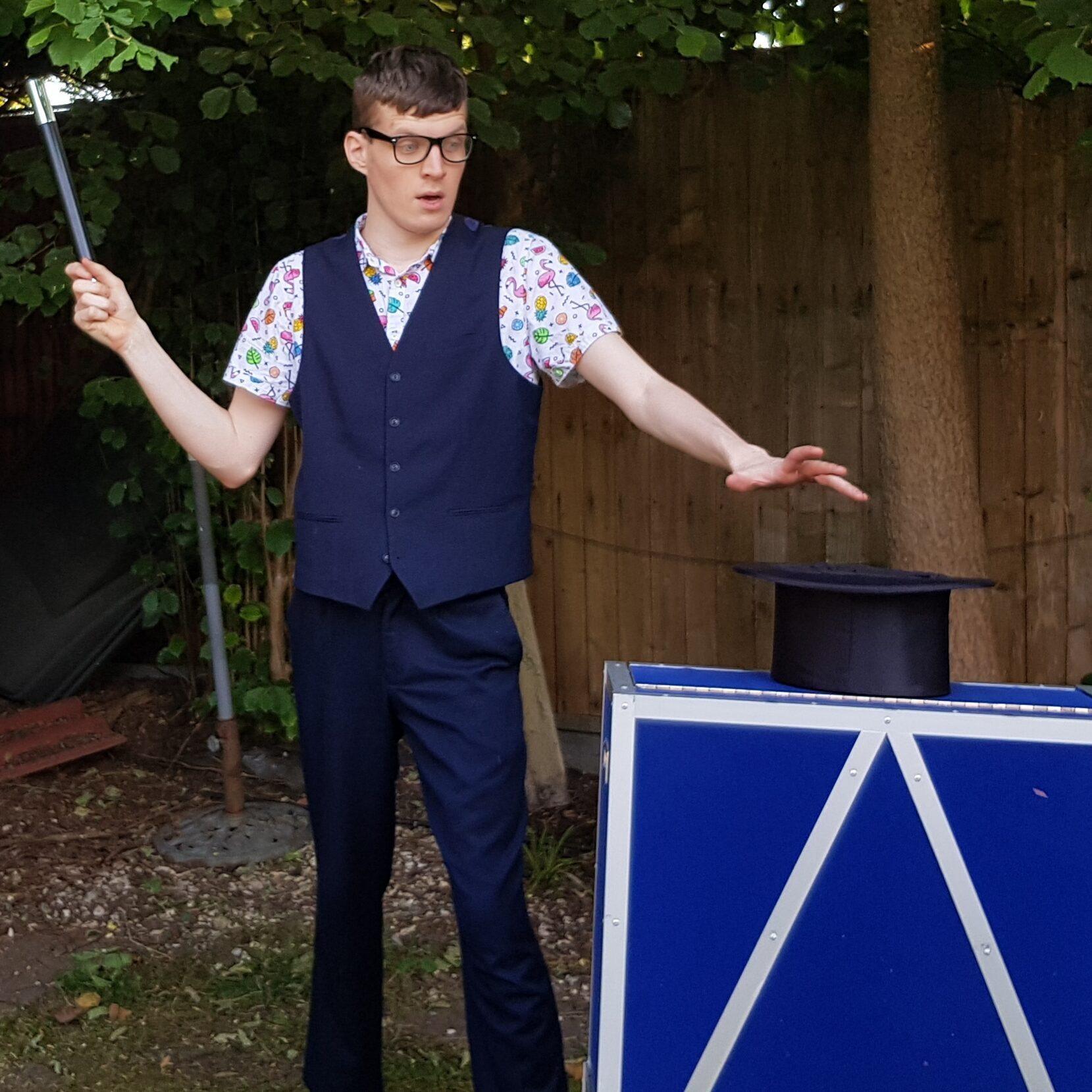 Harvo performing a magic trick with a magic wand and his magic hat