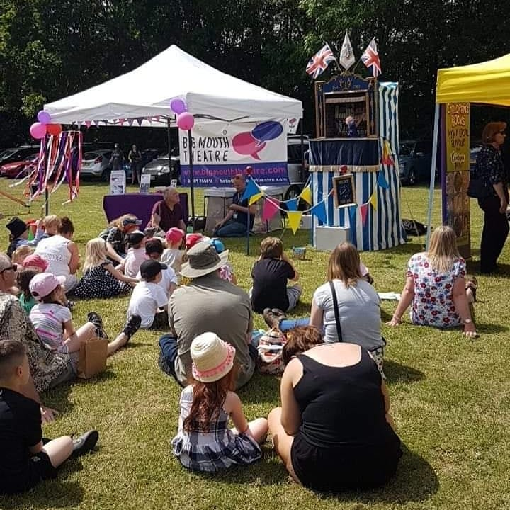 Image of a Punch and Judy Show on a large field with a big crowd